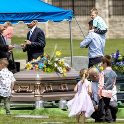 Rusty Butterfield looks down at his parents' caskets as he is carried by a family member after graveside services for Tony and Katherine Butterfield in the Herriman City Cemetery on Saturday, April 25, 2020. The couple was killed at their home in West Jordan on Saturday, April 18, 2020. Albert Enoch Johnson was arrested the following Wednesday in Stockton, California, in connection to the Butterfields' shooting deaths.