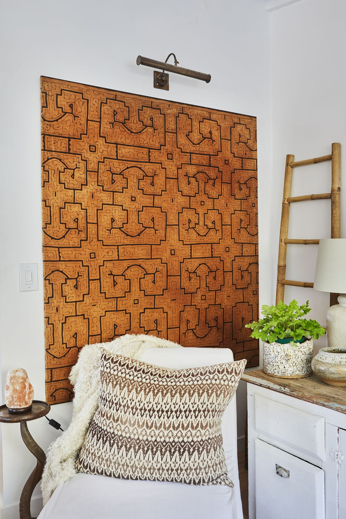 A brown-and-black tribal textile is stretched like a canvas and hung in the media area.