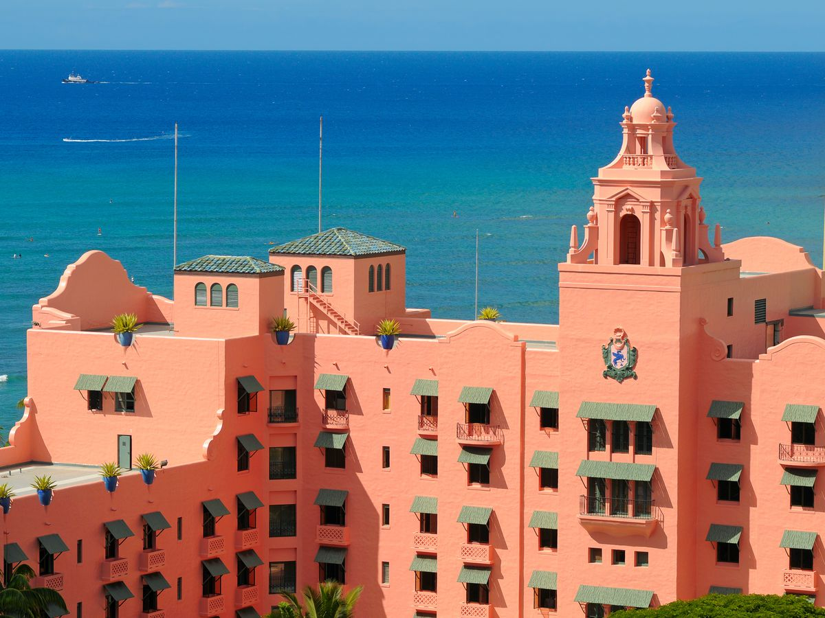 A pink hotel against blue waters of the Pacific.