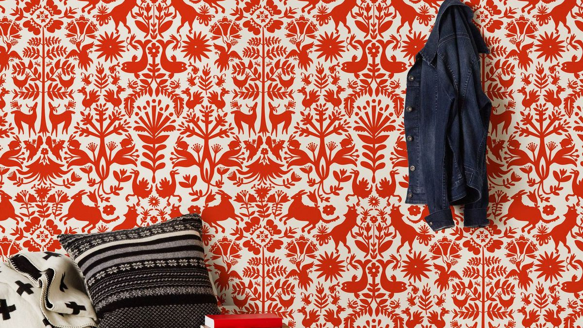 Pillows and a denim jacket hang in front of a red patterned wallpaper.