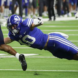 Brigham Young Cougars defensive back Morgan Pyper (10) dives for Arizona Wildcats Stanley Berryhill during the Vegas Kickoff Classic in Las Vegas on Saturday, Sept. 4, 2021. BYU won 24-16.