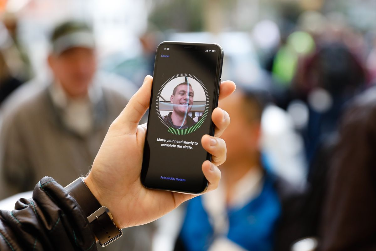A man holds an iPhone displaying the Face ID verification screen.