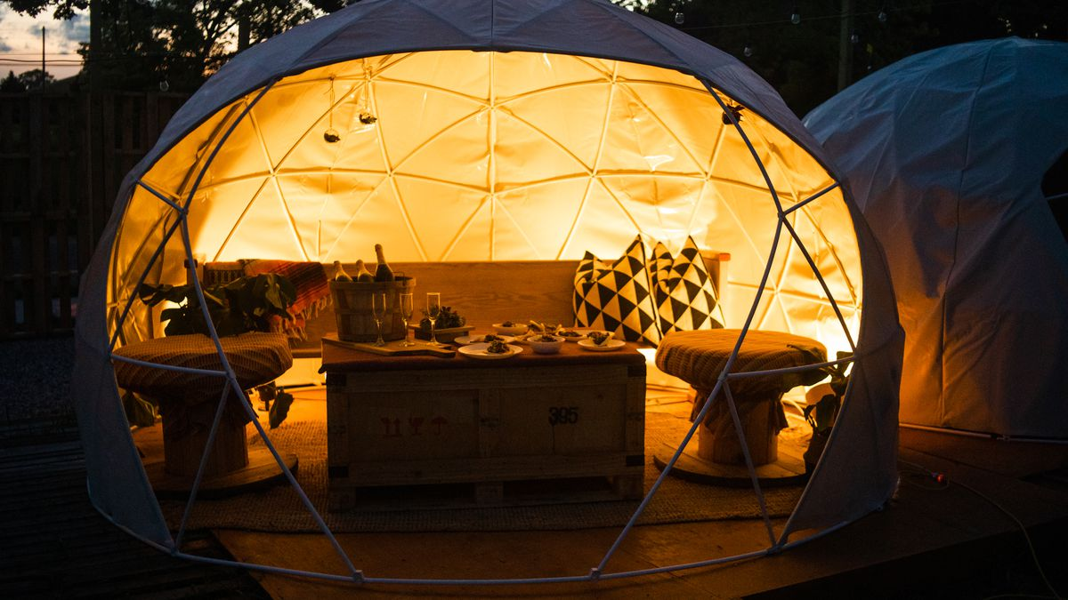 A geodesic dome is half open and filled with furniture. The interior glows at twighlight.
