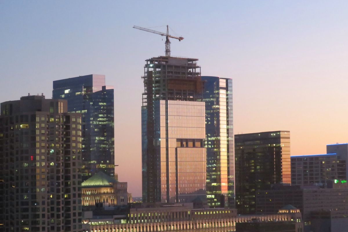 A glassy high-rise topped by a construction crane at dusk, reflecting the sunset. The building is surrounded by other similarly-sized skyscrapers.