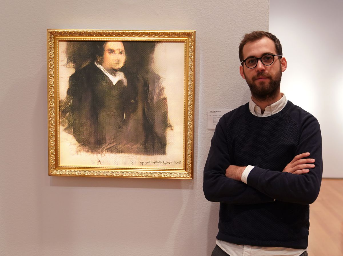 """Pierre Fautrel, co-founder of the French collective Obvious, stands beside an AI-generated painting titled """"Portrait of Edmond de Belamy."""""""