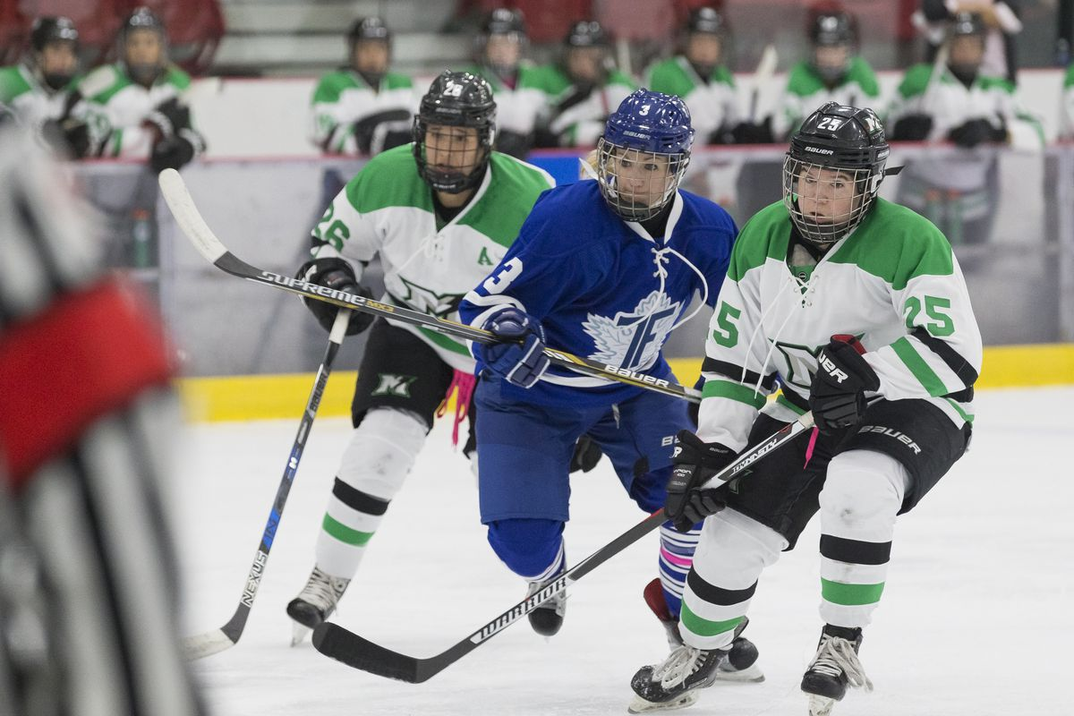 Hayley Williams, wearing Furies home blue uniform skates between Taylor Woods (in front) and Jamie Lee Rattray (coming up from behind), both wearing Thunder road whites with green accents.