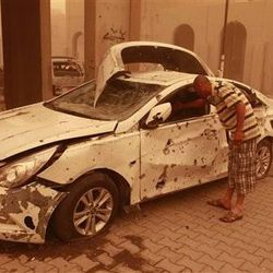 Mahmoud Ali inspects his destroyed car during a sandstorm after a car bomb explosion in Haifa Street, Baghdad, Iraq, Thursday, April 19, 2012. A wave of morning bombings across several cities on Thursday, killing and injuring dozens of Iraqis, police said, shattering weeks of calm in a reminder of the nation's continued insurgency. (AP Photo/Karim Kadim)