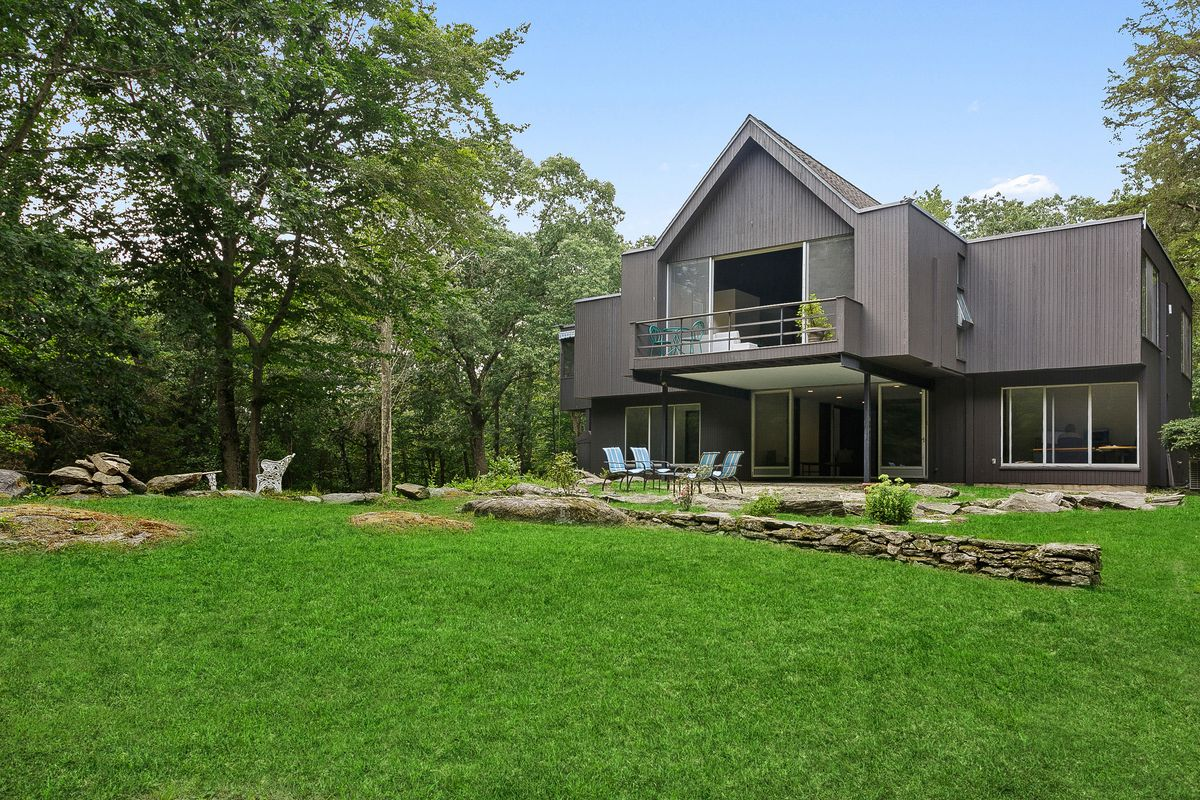 An exterior view of a gray modernist house with a peaked A-frame style roof and a patio.