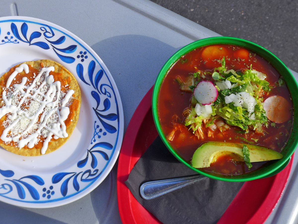 A bowl of bright red soup with a slice of green avocado floating in it, and a tostada on a side plate.