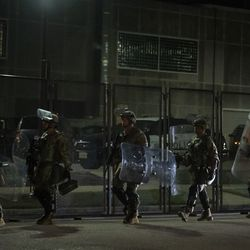 Hundreds of officers from agencies including, but not limited to, the National Guard and the Wisconsin State Patrol, arrive in five buses and file into the barricaded area containing the Kenosha County Courthouse and nearby municipal buildings on the fifth night of protests after police shot Jacob Blake, Thursday night, Aug. 27, 2020.