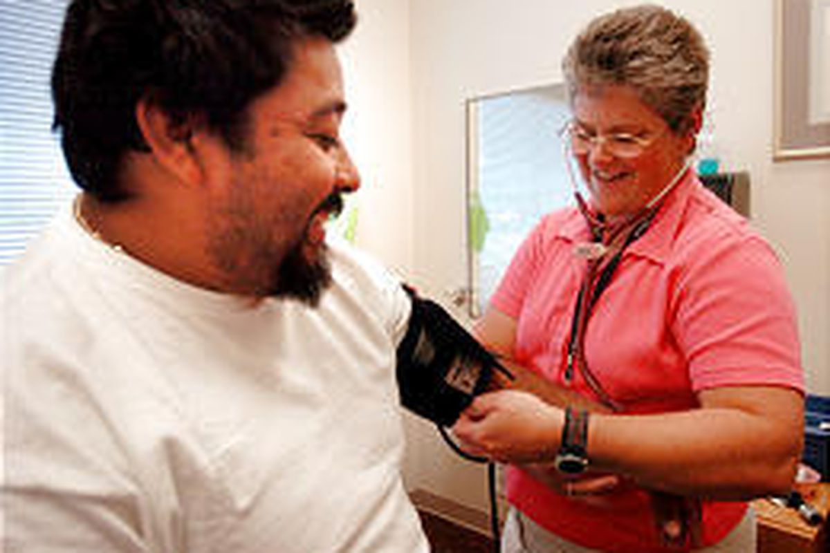 Alex Lopez shares a laugh with nurse Diane Kendall as she checks his blood pressure at Rose Park Elementary's clinic recently.