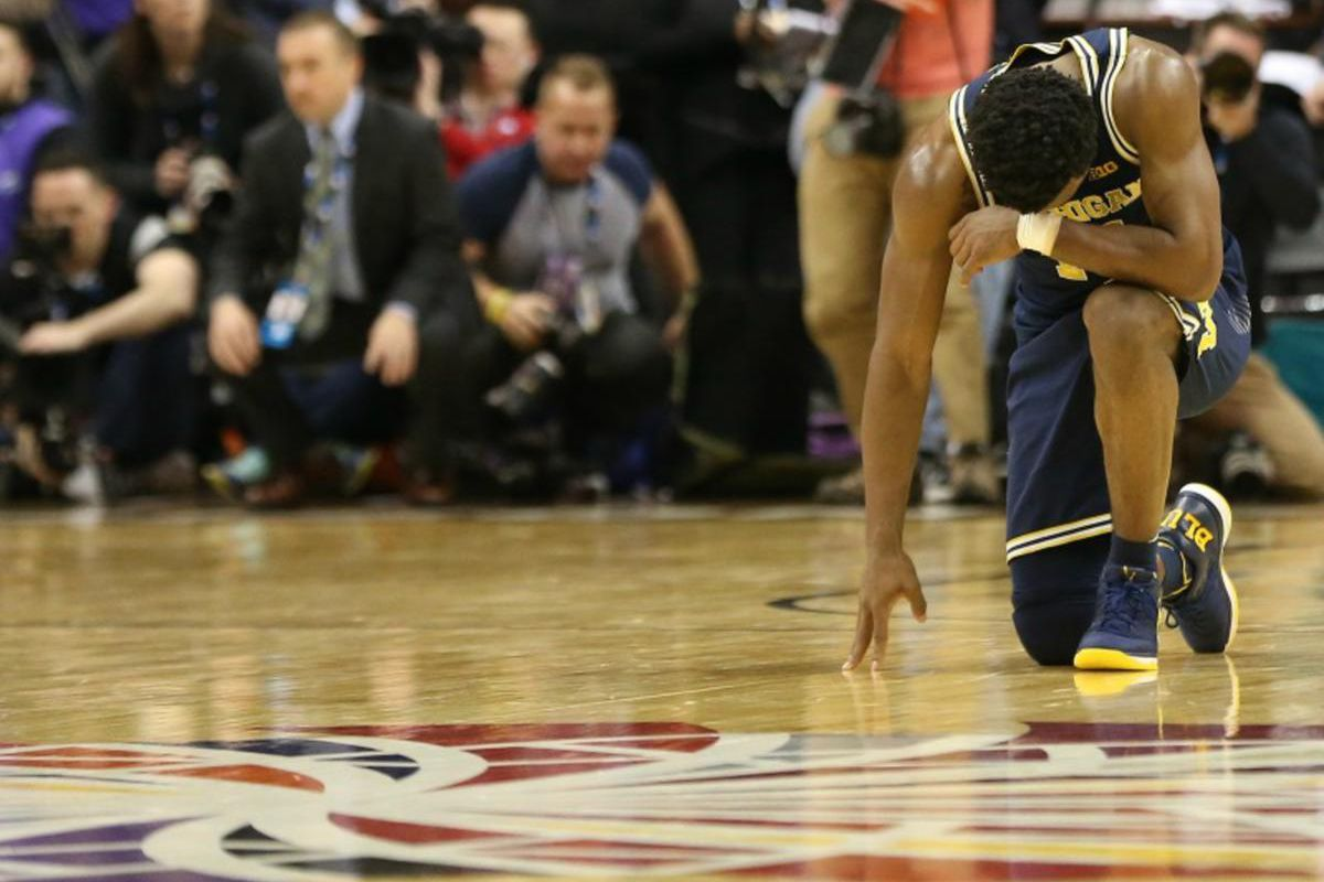 Michigan Wolverines guard Derrick Walton Jr. kneels on the court at the conclusion of the Wolverines\' game against the Wisconsin Badgers during the Big Ten Conference Tournament championship game March 12, 2017, at Verizon Center in Washington, D.C. The