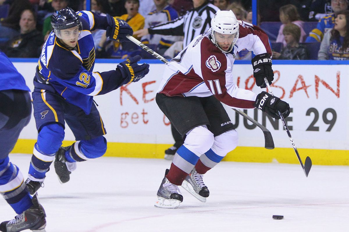 ST. LOUIS, MO - APRIL 5: Philippe Dupuis #11 of the Colorado Avalanche looks to beat Kevin Shattenkirk #12 of the St. Louis Blues to the puck at the Scottrade Center on April 5, 2011 in St. Louis, Missouri.  (Photo by Dilip Vishwanat/Getty Images)