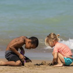 Isaiah Hart-Flowers, 7, on vacation and visiting his grandpa—a Maywood resident—from Phoenix, builds a sand castle with 4-year-old Mara Dues, of the Little Italy neighborhood, at 31st Street Beach on the South Side, Wednesday afternoon, July 24, 2019.