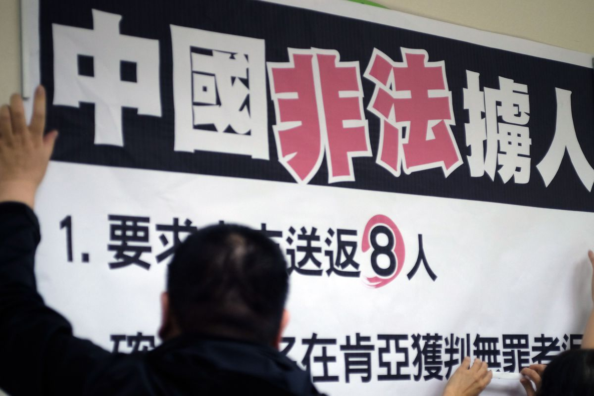 """Workers paste a sign reading """"China illegally abducts Taiwanese people"""" during a press conference organized by lawmakers from the Democratic Progressive Party (DPP) at Parliament in Taipei on April 12, 2016."""