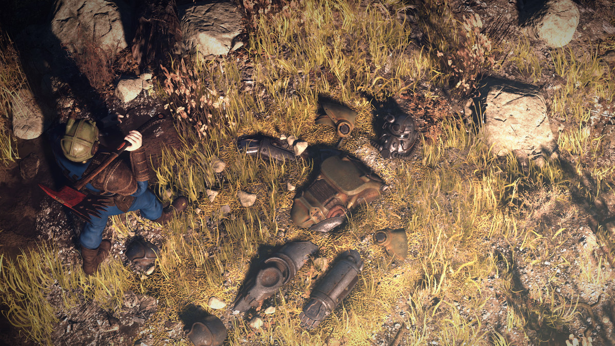 Fallout 76 - a man with a pickax walks past power armor partially buried in the ground