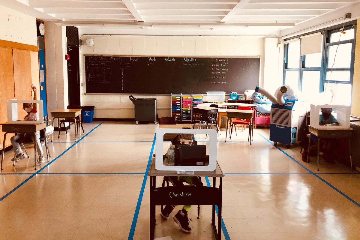 """Three masked elementary students sit behind clear shields placed on widely separated desks in a classroom with a portable air-conditioning unit. The blackboard has a """"Math Word Wall"""" and a space with """"Noun Verb Adverb Adjective""""  written, as well as the class schedule."""