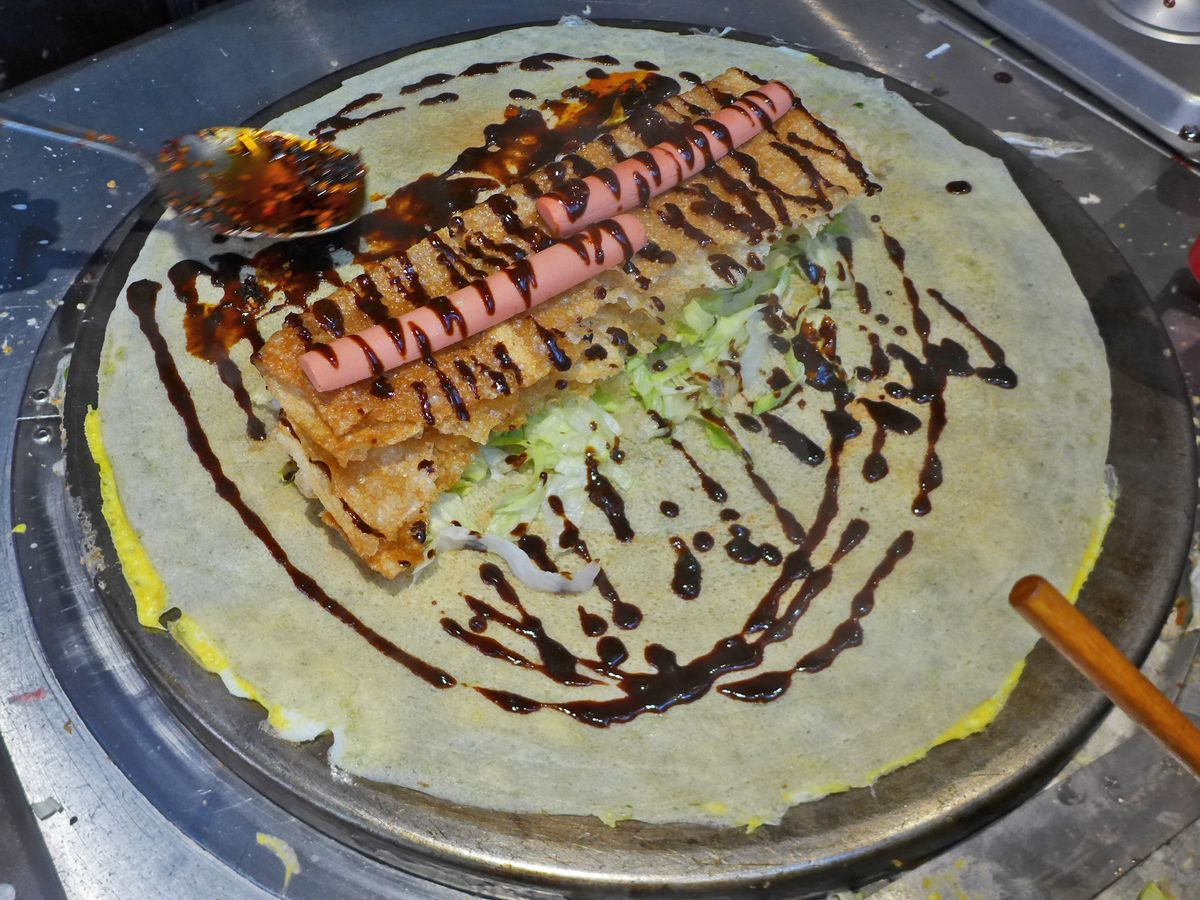 A pancake on a griddle with all sorts of things dribbled on it and a couple of hot dogs.