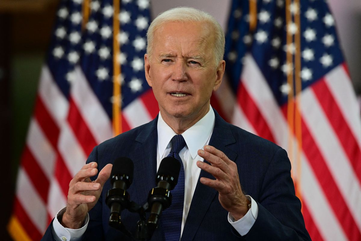 President Biden speaks into a microphone in front of several American flags.