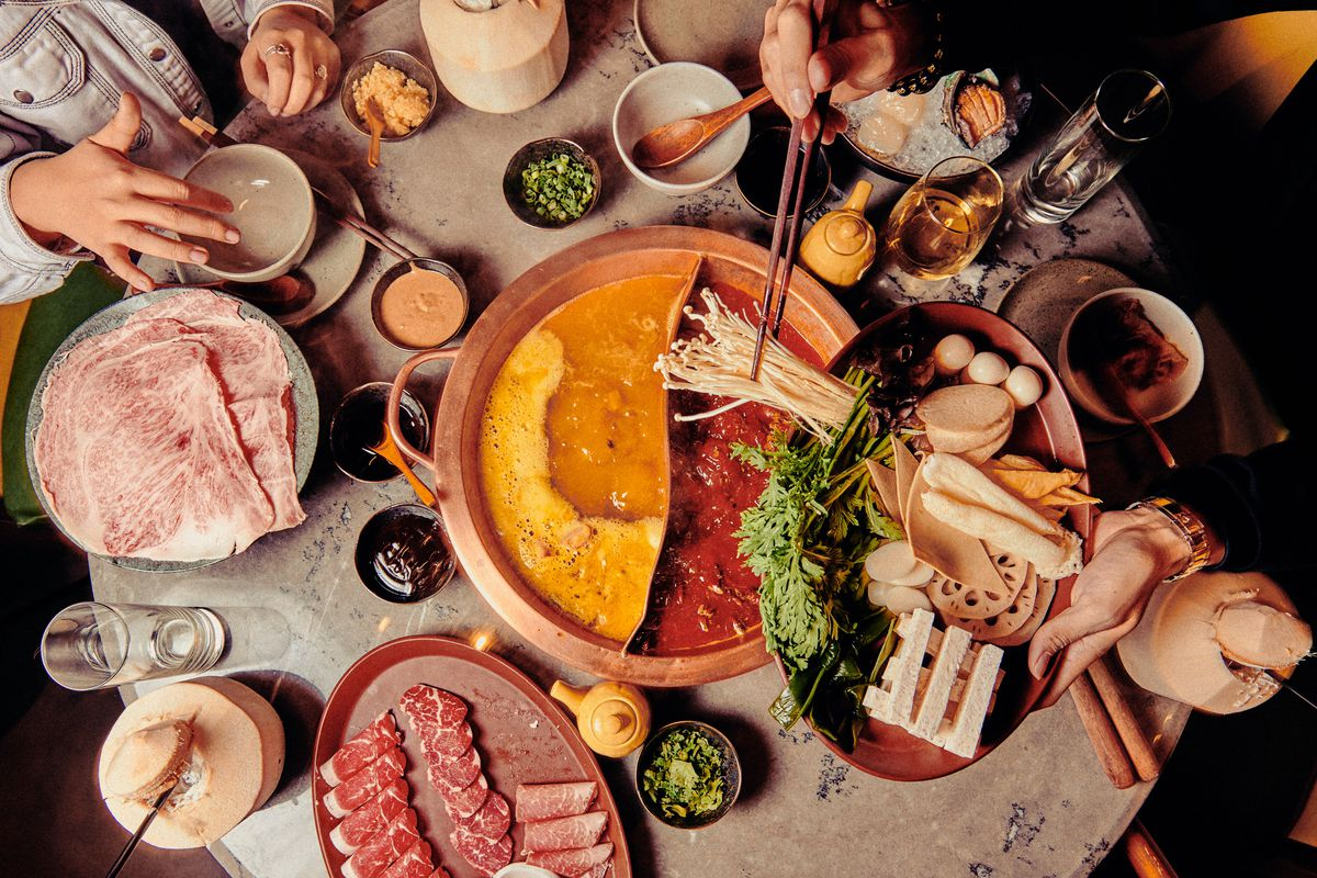 A table has a communal hot pot in the middle with two broth options, plus a spread of ingredients such as thin-sliced meat and enoki mushrooms