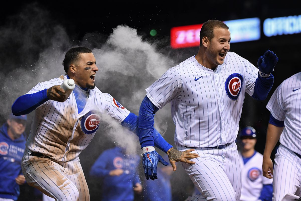Anthony Rizzo celebrates his walk off, 11th-inning  single with Javier Baez and other Cubs teammates Wednesday night.