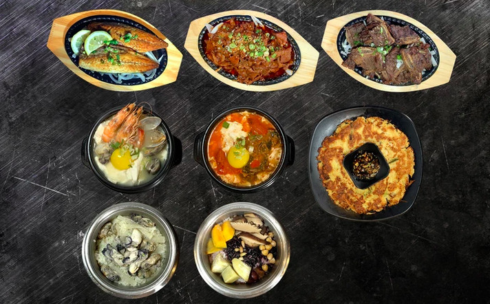 Overhead view of eight dishes of Korean food, spaced out over a black table