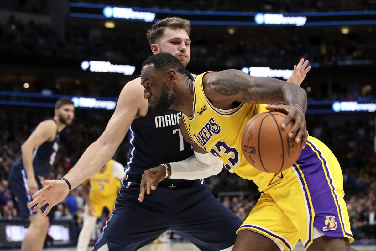 Los Angeles Lakers forward LeBron James dribbles as Dallas Mavericks guard Luka Doncic defends during overtime at American Airlines Center.