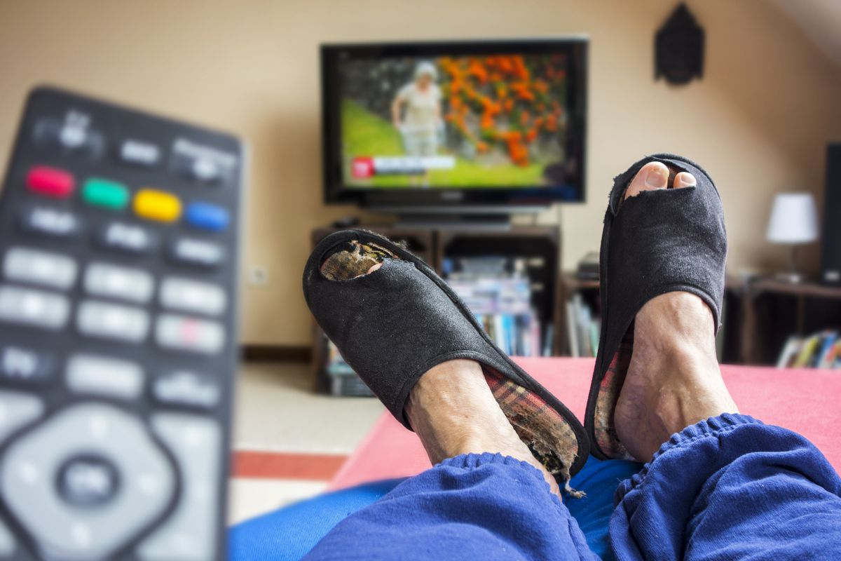Remote control and couch potato, lazy man in comfy chair wearing worn slippers with big toes sticking through and watching television in living room.