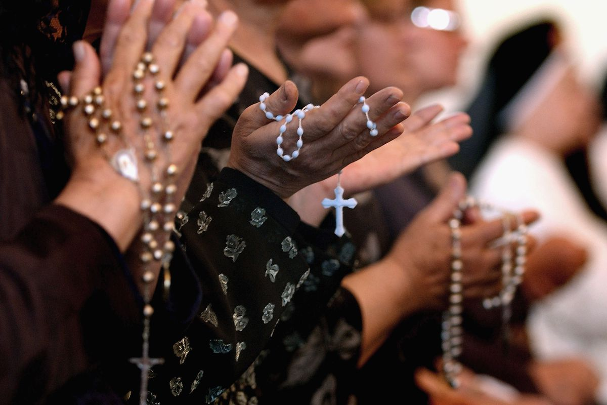 A close-up photograph of the hands of Iraqi Christians, who are praying and holding rosaries and crosses.