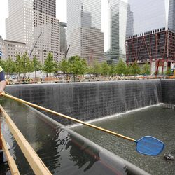 FILE - In this May 13, 2011 file photo, Anthony St. Jeanos, left, uses a net to skim debris from the water during a test of the waterfalls at the National September 11 Memorial, at the World Trade Center site in New York. The foundation that runs the memorial estimates that once the roughly $700 million project is complete, it will cost $60 million a year to operate.