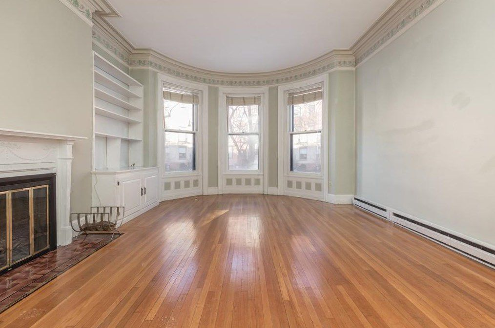 An empty living room with a fireplace and a bay window.