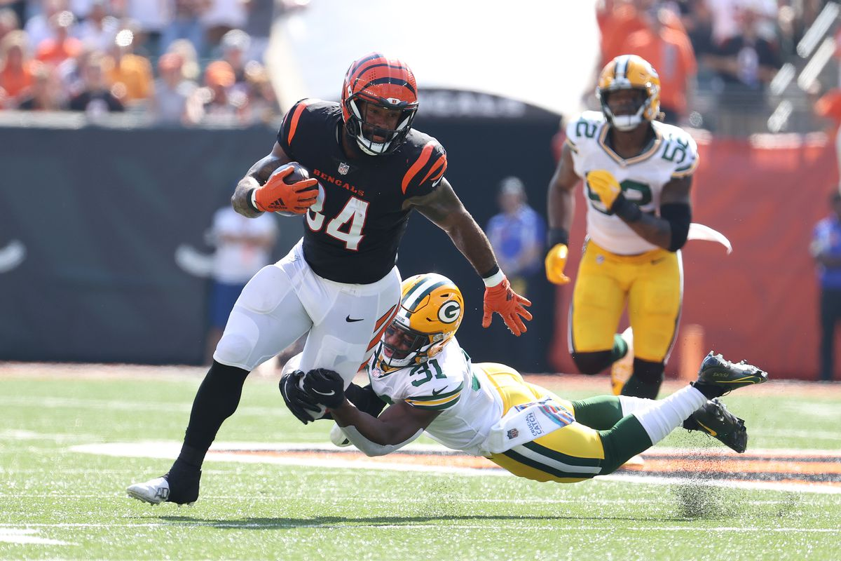 Samaje Perine #34 of the Cincinnati Bengals runs the ball and looks to avoid a tackle by Adrian Amos #31 of the Green Bay Packers during the first quarter at Paul Brown Stadium on October 10, 2021 in Cincinnati, Ohio.