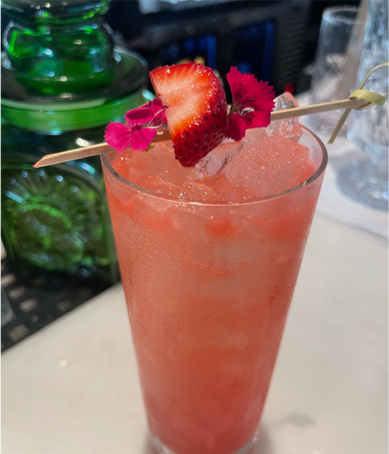 A pink cocktail with a skewer of strawberries and pink flowers