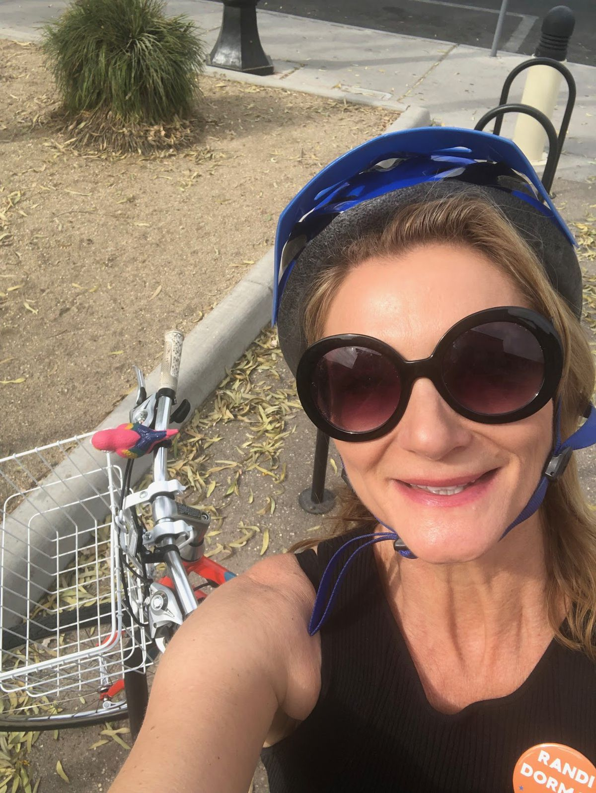 A middle-aged woman wearing a blue bike helmet poses with her orange bike.
