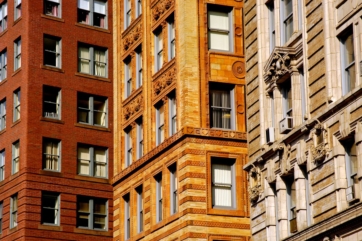 The exteriors of three apartment buildings in Boston. The center facade has orange brick. The facade on the left is red brick. The facade on the right is tan and white.
