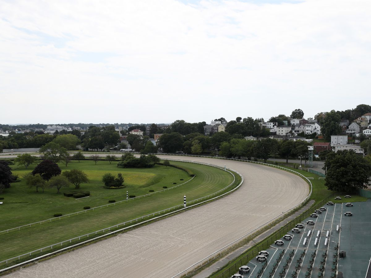 Empty bleachers facing the empty curve of a horse-racing track.