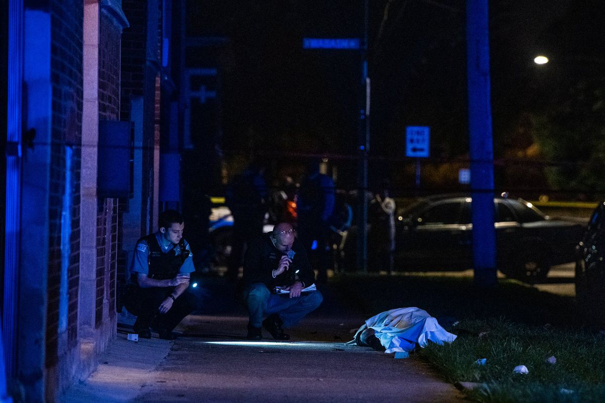 Chicago Police investigate the scene where a person was shot and killed in the first block of East 74th Street.