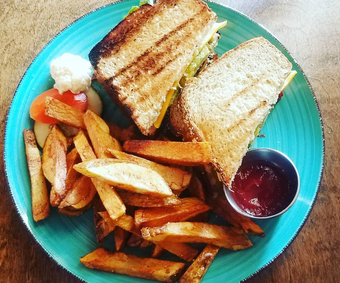 From above, a bright plate with a sandwich, steak fries, and ketchup