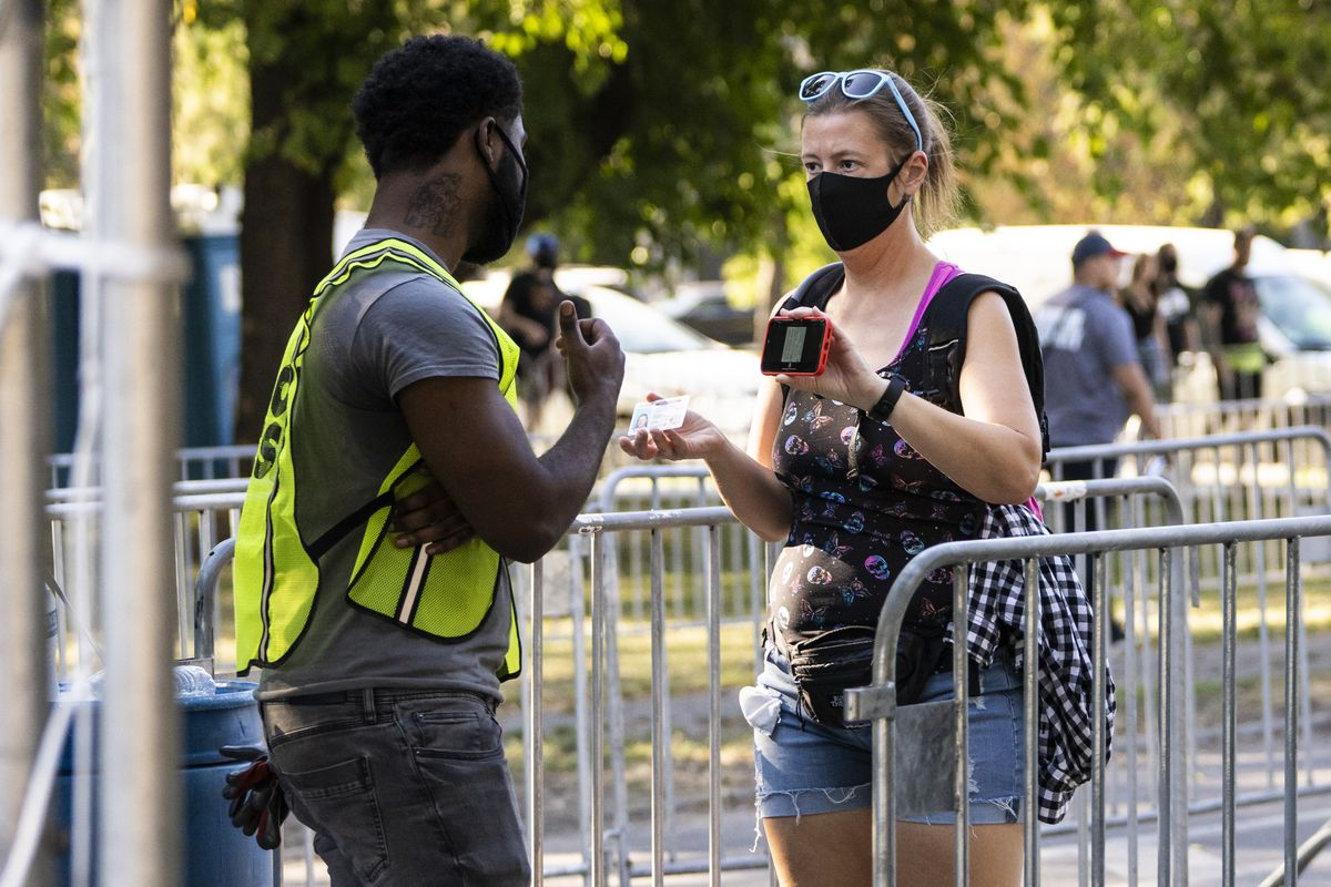 Security checks for proof of vax at the entrance of Riot fest on Thursday afternoon in Douglass Park.