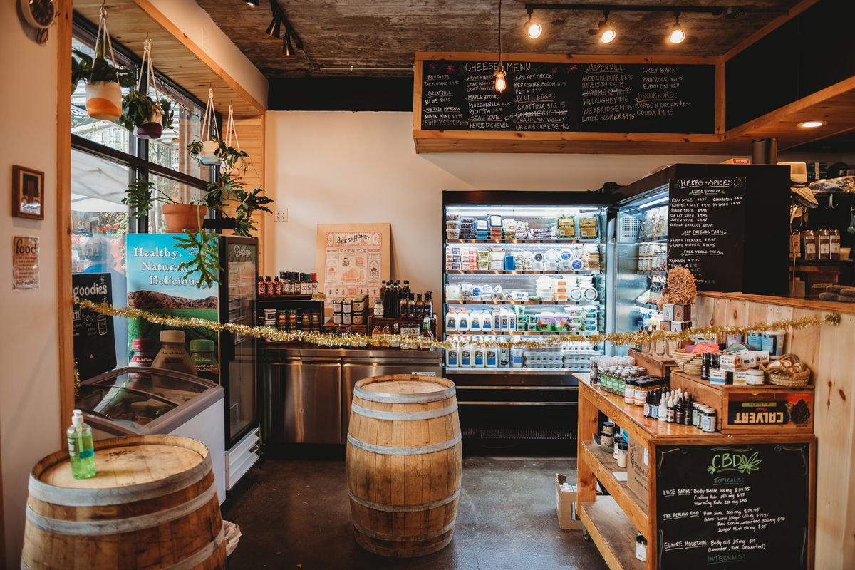 interior shot of a small specialty food store with a refrigerator and shelves full of local products