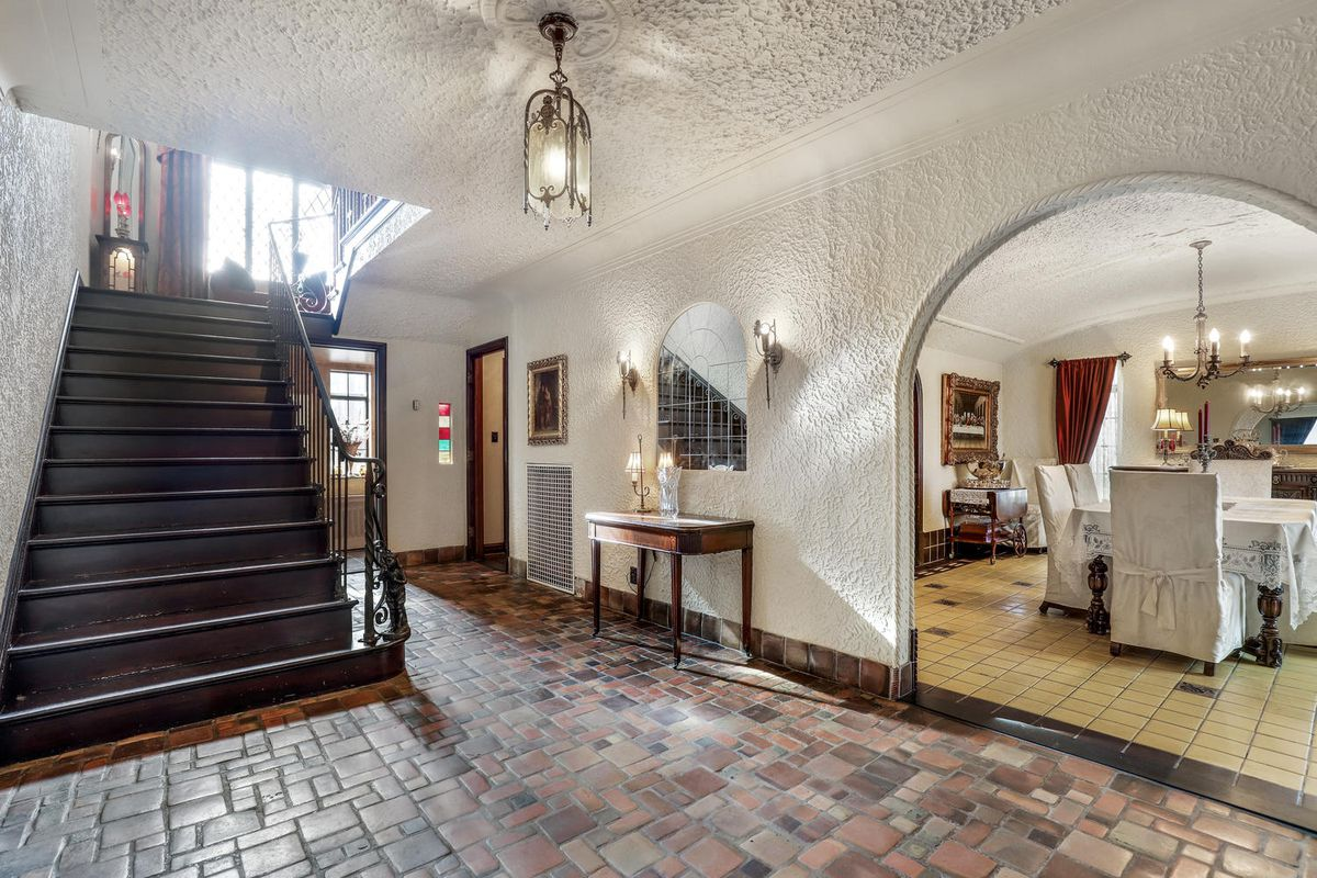 The floor of the vestibule is shades of brown tile. the stucco walls are white and there's a entryway leading to a dining room.