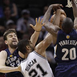 San Antonio Spurs' Tim Duncan (21) is defended by Memphis Grizzlies' Marc Gasol, left, of Spain, and Memphis Grizzlies' Quincy Pondexter (20) during the first quarter of an NBA basketball game on Thursday, April 12, 2012, in San Antonio.
