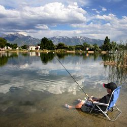 Jack Walpole stays cool by sitting in his chair in the water as he and his family enjoy the day at Murray's Willow Pond Park. Free Fishing Day in Utah Saturday, June 2, 2012. You didn't need a fishing license to fish in the state that day.