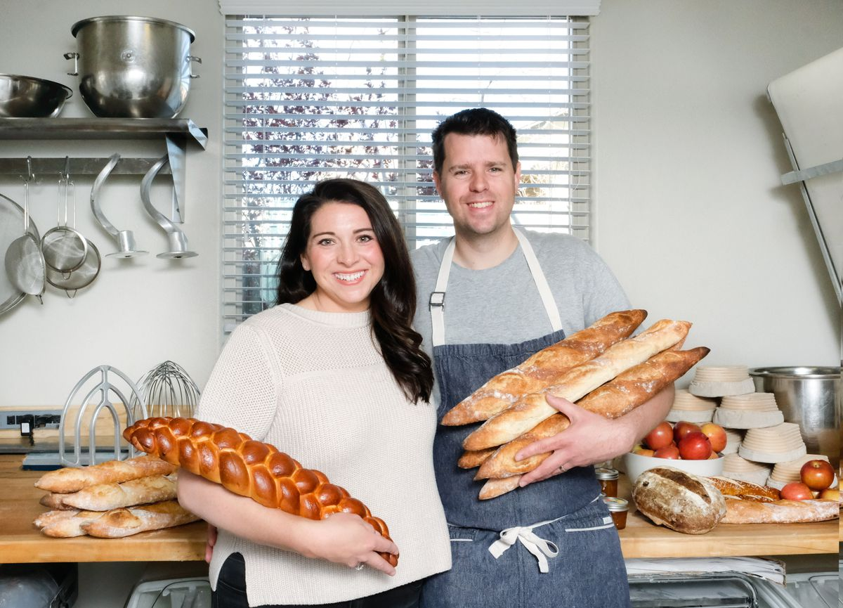 A woman and a man hold bread in a kitchen