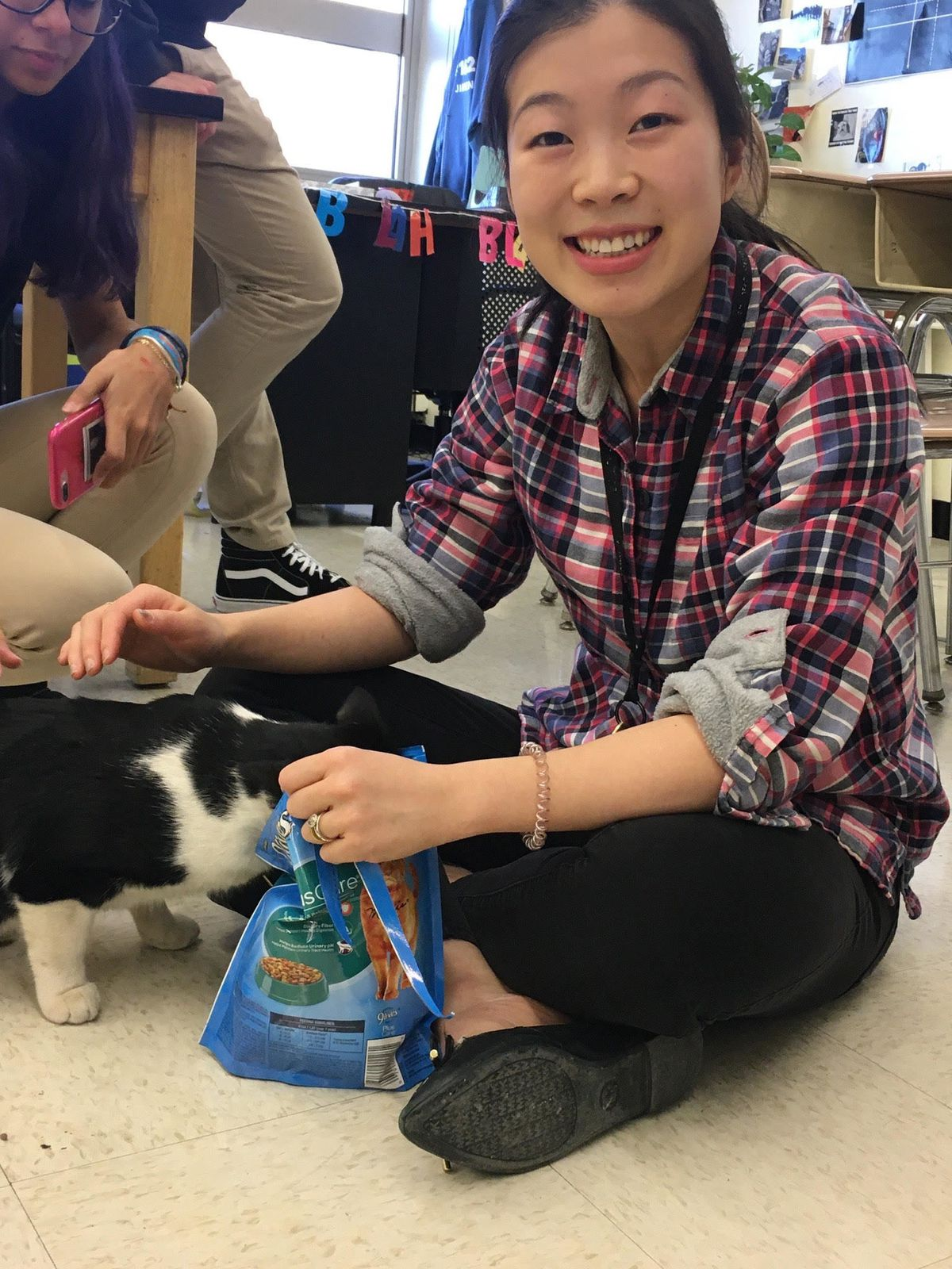Nancy Yeh is seated on the floor in a classroom, petting a black and white cat while holding a bag of cat food. She is wearing a bracelet, blue and red plaid shirt and black pants, and there is a young woman next to her.