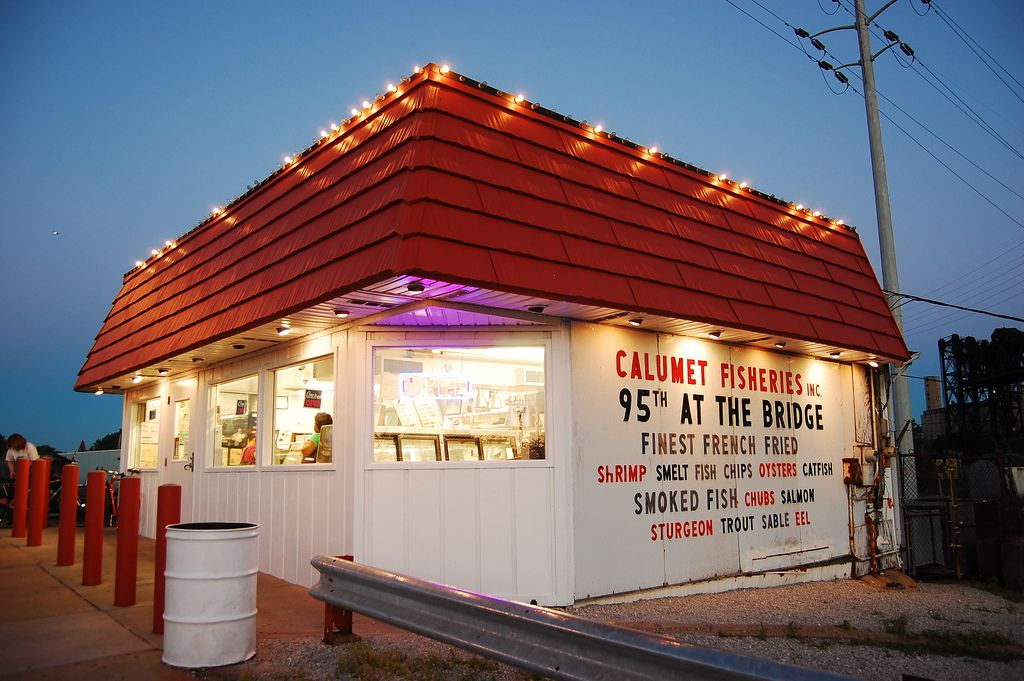"""A small white building with a red roof that reads """"Calumet Fisheries"""" in red letters."""
