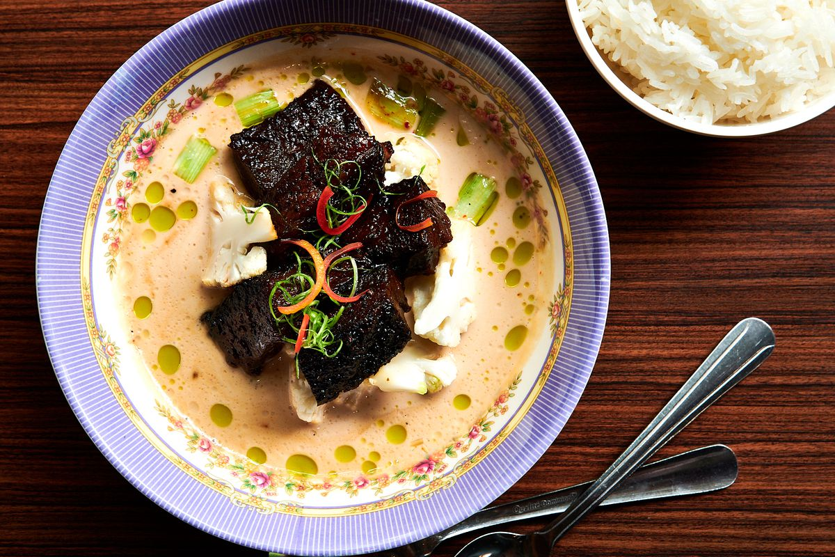 A bowl of white curry with hunks of brisket burnt ends