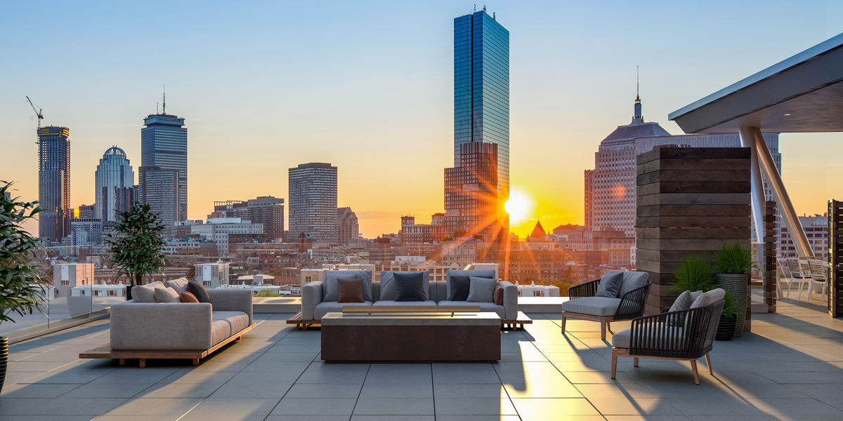Rendering of a roof deck with furniture and overlooking a city skyline.