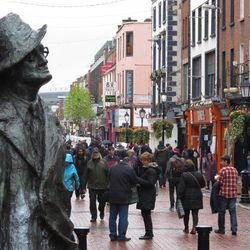 A statue of author James Joyce overlooks the scattered shoppers on Dublin's North Earl Street on Thursday, April 26, 2012. Ireland's economy has suffered four straight years of falling property prices and consumer spending in the face of rising taxes, unemployment and emigration. The European Union and International Monetary Fund said Thursday that Ireland's government must keep cutting its spending overall but do more to create jobs and stimulate the economy.