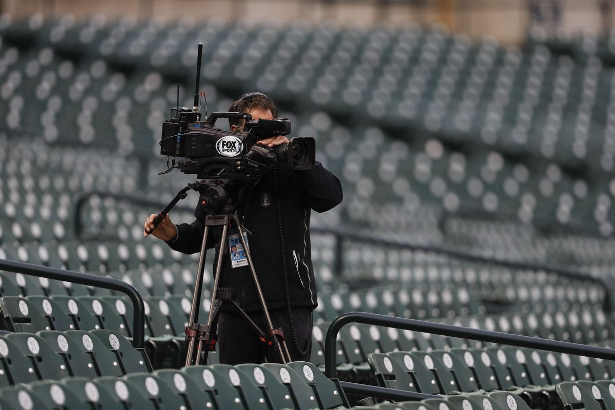 A Fox Sports camera man records from the empty bleachers near third base during the first inning in the game between the Detroit Tigers and the Milwaukee Brewers at Comerica Park.